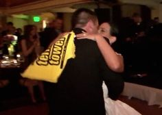 """A bride's arms are wrapped around her groom's shoulders as they share a kiss during their first dance as man and wife. In her hand is a yellow and black """"Terrible Towel,"""" a symbol of the couple's shared love for the Pittsburgh Steelers football team. In the background, the John Parker Band provides the soundtrack to this special moment at the Omni William Penn Hotel, Pittsburgh. http://www.jpband.com/weddings.html"""
