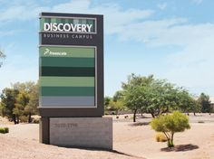 A double-sided illuminated ground sign with a block masonry base. The sign brands the Discovery name at the top while having six tenant panels available to different companies below.
