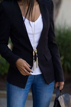 Shop this look on Lookastic: http://lookastic.com/women/looks/v-neck-t-shirt-blazer-pendant-ring-backpack-skinny-jeans/8278 — White V-neck T-shirt — Black Blazer — Gold Pendant — Gold Ring — Black Leather Backpack — Blue Skinny Jeans