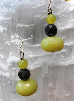 "Beautiful Faceted Chartreuse Green Chalcedony Stone at the Bottom With a Shining Faceted Silver Hematite in the Center and a Smooth Chartreuse Green Jade Topping off this Beautiful Trifecta Make for a Fun Splash of Color to Your Favorite Summer Outfit!     Earrings hang From Sterling Silver French Hook Approximately 1 & 1/2"" Long.   Chalcedony Bead at Bottom of Stack is Approximately 5/8"" Wide.  Jade Bead at Top of Stack is Approximately 1/4"" Wide.    Earrings come with Rubber Earring Backs…"