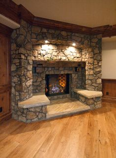 Love this rustic fireplace with lights on the mantle with stone seating on the sides.