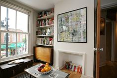 The trunk under the window, the sheet rocked fireplace, and the bookshelf and sliding door dresser in the corner. Love! Tamasyn's Colorful, Patterned London Flat