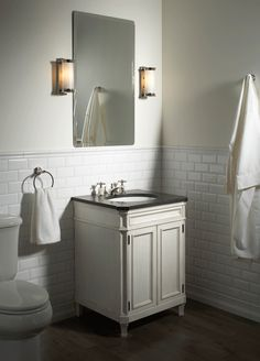 """ANN SACKS Arden 3"""" x 6"""" beveled ceramic field in white with @Kallista Plumbing classic cylinder wall sconce, for loft mirror, bellis wood vanity shown in antique french white, precut marble top in bleu de chine and amedee basin set with cross handles in honey onyx"""