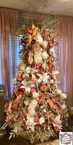 Gold and pinks on the Christmas tree with large pearl garland and feathers and flowers. Very wide ribbon as well as think spiral ribbons running down tree. Statement tree with wow topper