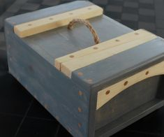 This is a simple take on the classic Japanese toolbox which features a wedge to close the lid together. It has a two tone design, parts of it stained and a rope...
