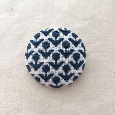 こぎん刺しの技法を用いて作ったブローチです。40ミリのブローチ用キットを使用しています。花の模様を、白地の布に紺色の糸で刺繍し、これからの季節にぴったりのブローチに仕上げました。シンプルなお洋服やストール、バッグなどのワンポイントにおすすめです。