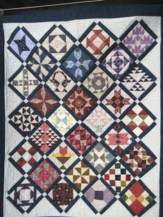A quilted wall hanging / sofa quilt / lap quilt This quilt features 32 different pieced blocks using fabrics that are reproductions of those