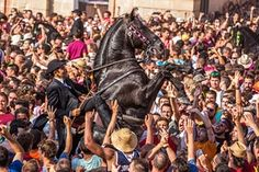 Crowds gather around a horse at the start of the annual medieval festival of Saint Joan in Ciutadella de Menorca. The event begins when the knights arrive, galloping into the main square of the town