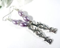 Presenting a pair of long elegant love charm earrings. These boho chic fashion earrings are created with love charms and violet gray glass beads on silver plate ear wires. This pair of love earrings dangle 2 ¾ inches from top of ear wires to bottom of charms.
