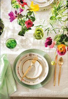 00456478. Cubiertos en dorado, verde y blanco y flores de varios colores en pequeños jarrones sobre la mesa_00456478