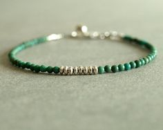 This minimalist turquoise bracelet has lovely natural round turquoise surrounding sterling silver beads at its center. This stand-alone or layering bracelet closes with a sterling lobster clasp, and a sterling Hill Tribe round bell charm.  The turquoise in this bracelet is a rich blue-green, and looks beautiful against the sterling silver. The simple minimal design of this bracelet makes it perfect for layering, or for wearing alone for a refined look. The optional round Hill Tribe sterling…