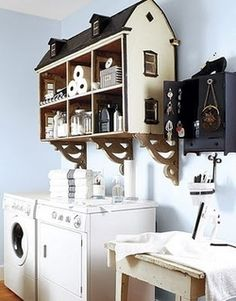 A dollhouse repurposed as shelving unit for laundry room.