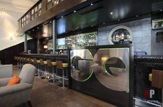 Акцент вытянутого помещения – длинная барная стойка обтекаемой формы. Она облицована антрацитовым битым стеклом и заказывалась в Китае. Стена за ней выложена серым сланцем, поставщик «Альпари СТК».