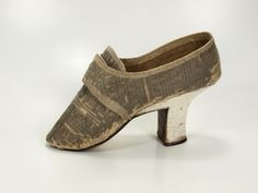 Pair of women's shoes, 1770-1780. Silver silk brocade, white silk ribbon, white leather covered high heel.