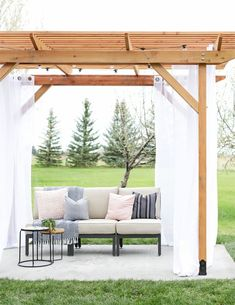 DIY Redwood Pergola with Free Building Plans | This outdoor pergola is stunning! Love the string lights and outdoor curtains.  #RedwoodDIY #JustRedwood #ad
