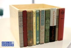 used book spines on a box. AMAZING upcycle for hiding toys in the living room.