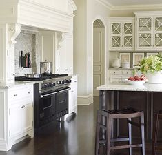 I love the molding surrounding the hood...also the paned glass cabinet doors.  I would love to cook here! @Suzanne Kasler