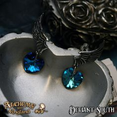 Alchemy Gothic ULFE15 El Corazon Dropper Earrings (pair)  A pair of pewter wing studs with blue heart Swarovski crystal droppers, on surgical steel ear-posts.
