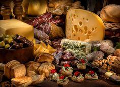 quesos y jamones en el campo - Una mesa de jamones, fiambres y quesos para deleitarse en el campo.