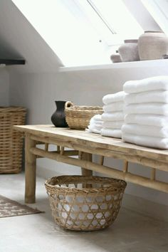 Bathroom with white towels and woven baskets