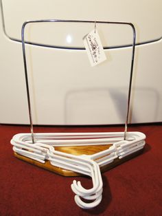 Clothes hanger organizer stand for the laundry room and bedroom closet with wood base and metal frame.