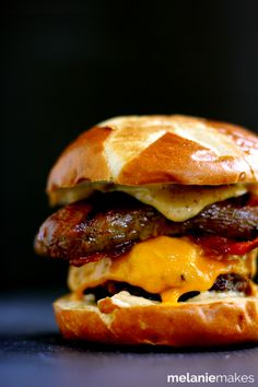 A quarter pound beef burger is topped with cheese, brown sugar glazed bacon and a split bratwurst.  This glorious mountain of meat is then sandwiched between two halves of a pretzel bun slathered with smoky mustard.  Forget the sides!  This Sweet and Smoky Bacon Brat Burger is a complete meal!