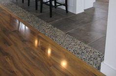 Dark ocean pebble accent tile used as transition from tile to wood. - Dark ocean pebble accent tile used as transition from tile to wood. Tile To Wood Transition, Transition Flooring, Transitional Living Rooms, Transitional House, Transitional Lighting, Transitional Bathroom, Entryway Chandelier, Living Room Wood Floor, Kitchen Flooring