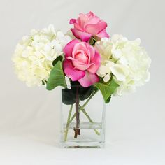 This artificial design features several white hydrangeas mixed with some real touch fuschia pink roses in a tall square glass vase. The arrangement looks simple and realistic that one cannot tell the different with fresh flower arrangement. The vase is filled with faux water inside so it can keep all pieces in place.  Height: 12 Width: 12  Visit my blog for past projects, customer photos and general information on real touch faux arrangements for wedding and home decor…