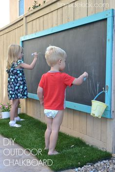 How to make a giant outdoor chalkboard for your yard. This is such a perfect outdoor activity for the kids and it has held up for over 2 years! kids play area outdoor playset How to Make a Giant Outdoor Chalkboard Kids Outdoor Play, Outdoor Play Spaces, Kids Play Area, Backyard For Kids, Backyard Projects, Diy For Kids, Childrens Play Area Garden, Kids Yard, Kids Fun