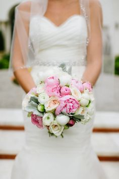 A classic beauty holds her classic bridal bouquet of pink, blush and white peonies, garden roses, ranunculus and dusty miller.