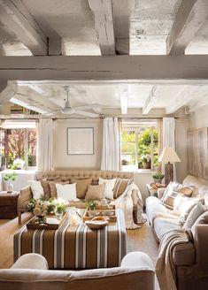 Salón con techo de vigas blancas y con sofás y mesa de centro-puf_ 00462181