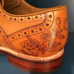 Rose tattoos on tan brogue shoe