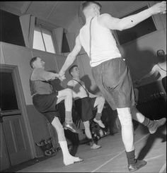 FACTORY WELFARE WORK: WELFARE AT PILKINGTON'S GLASS FACTORY, ST HELENS, LANCASHIRE, ENGLAND, UK, 1944 D 20093  Men with leg and back injuries perform balance exercises in the gymnasium at the factory rehabilitation centre, (probably at Pilkington's glass works at St Helens), as part of their recovery programme. The men are standing in a circle and holding...