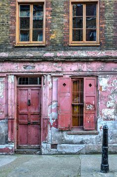 The pink peeling entrance to 4 Princelet Street, Fournier Street and Brick Lane conservation area, Spitalfields, London, UK. The house is a double fronted Georgian merchants house from the early 18th century. The interior is conserved in it's original condition.