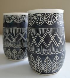 These tumblers are wheel thrown, painted with a black velvet underglaze, and include hand carved designs. Inside of tumblers are glazed with a matte clear finish allowing the natural color of the white clay to show through. These ceramic stoneware vessels are dishwasher and microwave safe, but do prefer to be hand washed.  Natural fired clay is perfect for keeping your cool beverages cool and your hot ones hot! This set also makes a great wedding or anniversary gift.  Cheers to one of the…