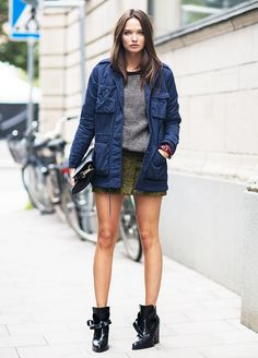Navy field jacket worn with a green mini skirt and black ankle boots