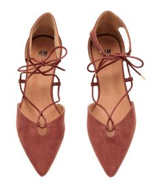 Flats in imitation suede with pointed toes, open sides, and lacing. Imitation leather lining, imitation leather insoles, and rubber soles.