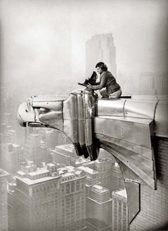 Oscar Graubner - Margaret Bourke-White perches on an eagle head gargoyle at the top of the Chrysler Building and focuses a camera, New York, 1935.