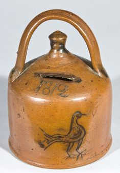 "$ 5980 Rare Stoneware Presentation Bank with Incised Bird, Dated 1812, Conn. origin, with rounded foot, button-shaped finial and unusual rainbow handle, decorated with an incised bird with feather detail below the incised date 1812. Reverse incised ""M.O.W."". Surface appears to be covered in an Albany slip glaze. This bank includes documentation made in 1884 of the bank's maker and owner. It reads ""This 'Bank' made of pottery, I purchased of Mrs. Benj F. Webster of Hartford Conn., bought 1884..."