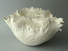 Alice Riehl - Needlework pieces  are dipped into liquid porcelain. The textiles remain inside the porcelain until fired. The textiles burn out, but they leave their shape in the porcelain.