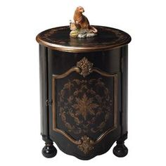 Hand-painted wood end table with antiqued brass hardware and bun feet.Product: End table  Construction Material: Selected hardwoods  Color: European black   Features:   Hand-painted   One door with antique brass hardware  Distressed   Enclosed storage Dimensions: 24.5 H x 18 Diameter