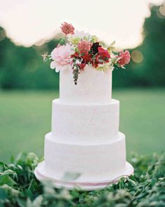 A Romantic, Flower-Filled Wedding in Oklahoma | Martha Stewart Weddings - There were three wedding cakes, with the largest of the trio—this multi-tiered confection—boasting the couple's vows written on the icing and fresh flowers in the day's color palette. Inside, the flavor combos were vanilla bean with vanilla mousse filling, strawberry cake with strawberry puree, and lemon cream cake with raspberry puree, all enrobed with buttercream icing.