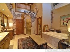 With medieval flair, this master bathroom features brick accents and stained glass windows. It also boasts tumbled tile floor, dual vanity, large soaking tub, and separate shower with a frame-less glass door. Castle House, House, Home, Master Bathroom, Tumbled Tile Floor, Brick Bathroom, Luxury Bathroom, Walkin Shower, Bathroom Inspiration