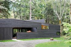 """The cedar siding is simply stained with a black semi-transparent oil stain [from Cabot], which allows the color of the wood to still emerge through,"" architect Robert Hutchison says. ""We love how the black color makes the building recede into the background, and how it in turn allows the trees on the site to emerge as the highlight.""  A standing seam metal roof by Custom Bilt Metals blends in with the cedar siding."