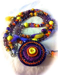"""Collar XLL """"Paz y amor"""" , con rosetón en 3 colores, tira de cristales facetados violetas, bolitas de madera naranjas, piezas variadas en resina, 6 charms corazones y estrellas con 6 pompones de algodón. Terminado con 3 pompones de algodón montados en anilla. 25€"""