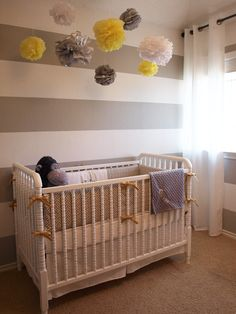 Adorable yellow & gray boy's striped nursery design with white & gray horizontal stripes painted walls, white Jenny Lind Crib with Waverly Cross Section Charcoal fabric crib bumper, mustard yellow ribbons and yellow & gray pom poms. Grey Yellow Nursery, Striped Nursery, Striped Walls, Nursery Neutral, Gray Yellow, White Walls, Nursery Room, Kids Bedroom, Nursery Decor