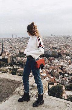Tricô de gola alta com listras nas laterais, calça jeans azul, coturno preto