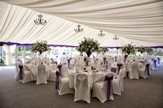 A luxurious Cadbury's Purple themed interior decor in the marquee with large martini glasses for the flower arrangements - http://www.whiteorchidphotography.co.uk