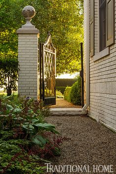 A wrought-iron gate at the side of the house separates the back and front gardens. - Photo: Bob Stefko