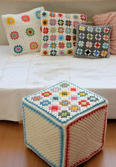 Photo of some pretty crochet pillows - I like the different sized granny squares and the ottoman is something I've never seen before.